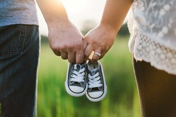 Family Holding Child's Shoes